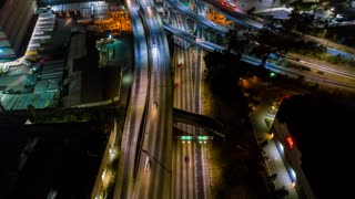 Urban aerial time lapse along city freeway and roads from above at night