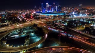 Urban aerial time lapse of downtown Los Angeles convention center, skyline and freeways with traffic at night.
