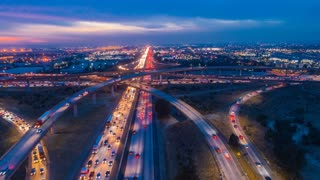 Urban aerial timelapse at night with interstate traffic