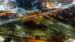 Urban aerial timelapse in motion or drone hyperlapse at night over a busy traffic circle and freeway onramp.