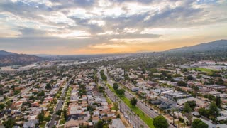 Urban aerial timelapse in motion or drone hyperlapse at sunset with a cinematic city view of a Los Angeles freeway and neighborhood intersection with city traffic below and clouds above