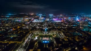 Urban aerial timelapse in motion or hyperlapse at night with busy street traffic and high-rise buildings below.