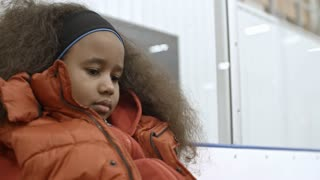 Cute little African girl sitting in ice arena and listening to female coach while she tying her skates