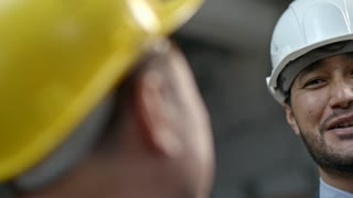 Close up with PAN of cheerful Asian supervisor in hard hat talking to unrecognizable male factory worker