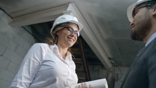 Tilt down of cheerful female construction engineer in glasses and hard hat holding blueprints and talking to unrecognizable businessmen, then smiling and shaking his hand