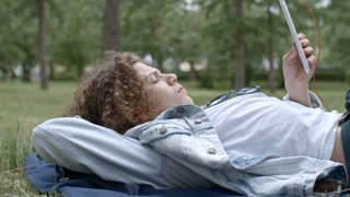 Teenage boy lying on green lawn in park, listening music with headphones and using digital tablet