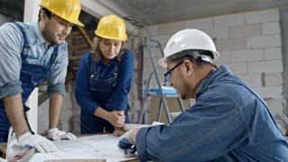 Medium shot with slowmo of mature foreman wearing glasses and hard hat sitting at table in unfinished building and discussing floor plans with Asian builder and female construction worker