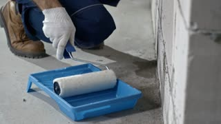 Tilt up of concentrated male Asian worker in blue overalls putting priming coat on brick wall with paint roller