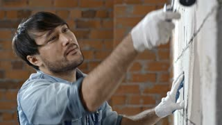 Tilt down of cheerful male Asian construction painter putting priming coat on brick wall with paint roller