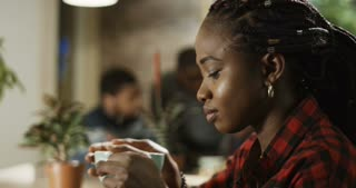 Very close shot of young black beautiful African girl sitting in cozy cafeteria and drink coffee with three chatting guys in the background. Shot on Red cinema camera.