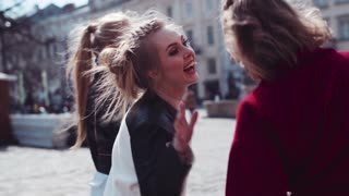 Very happy girls having fun in the city center, hugging and laughing. Leisure time. Time to relax. Friendly atmosphere. Sunny weather. Urban settings on the background.