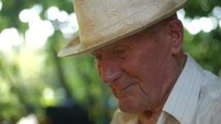 Very old man portrait with emotions. Grandfather in white hat sad and depressed. Portrait: aged, elderly, loneliness, senior. Close-up of a pensive old man sitting alone outdoors. Slow motion
