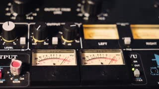 View on sound check gauges moving rhytmically in tempo of music beat, located on professional sound board panel in production studio