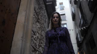 View tourist woman walking narrow streets of Barcelona. Wearing cute summer colorful dress enjoying European summer holiday travel vacation adventure. Slow motion
