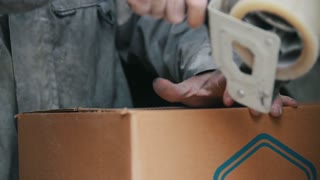 Warehouse workers packing up box with sticky tape in a industrial warehouse