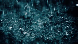 Water drops hitting foamy surface in the dark close-up slow motion video
