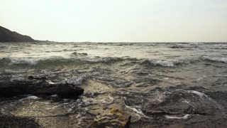 Waves in a troubled sea on the shore after a storm are broken against stones slow mo