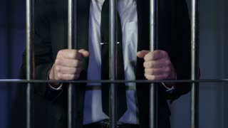 White Collar Crime Zoom Out From Hands On Prison Bars