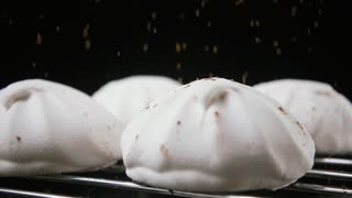 White marshmallows, on a stand, sprinkle cocoa powder, on a black background. Slow motion