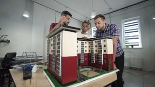 Wide angle of young diverse group of co-workers architects discussing by miniature of building in office