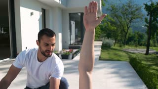 Woman And Man Doing Stretching And Fitness Togetheron terrace of beautiful villa