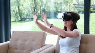 Woman At Home Wearing Virtual Reality Headset