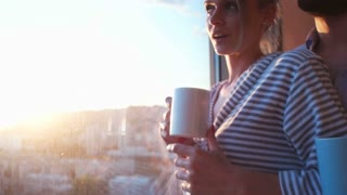 Woman Drinking Coffee By The Window With Cityscape View during sunset
