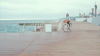 Woman in sport clothing riding white vintage bicycle on seaside during cloudy rainy day