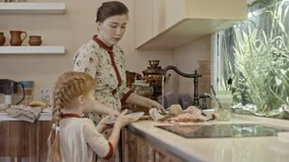 Woman in traditional Russian dress washing dishes in sink while her husband and three kids eating homemade bread and drinking tea at kitchen table