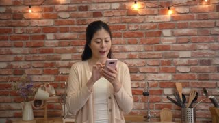 Happy Asian woman receives good news text on her phone