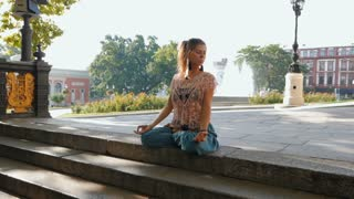 Woman meditating in lotus position on top of stairs. Young girl in blue pants doing yoga on busy city background. slow motion