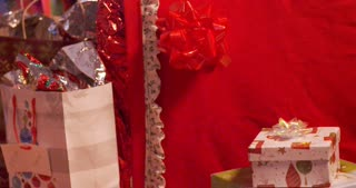 Woman places a present at the bottom of a Christmas tree