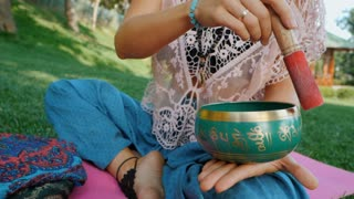 Woman playing singing bowl while sitting on pink yoga mat in park at summer. Vintage tonned. Beautiful girl with mala beads meditating on green grass. Slow motion