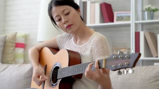 Asian woman playing the guitar in the living room