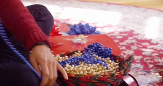 Woman pulls beads out of bowl to decorate the Christmas tree.