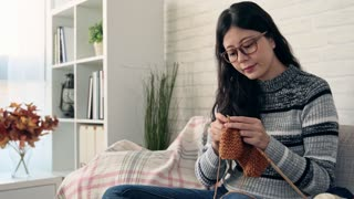 Asian woman knitting while sitting on sofa looking outside