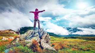 Woman standing on top of a mountain with hands rised up. Back view. Majestic autumn landscape. Beauty world, sport lifestyle, holidays, travel and recreation. Carpathians, Ukraine. Slow motion 4K