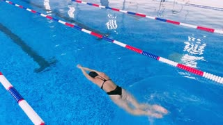 Woman swimming in a swimming pool. Slow motion.