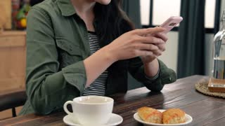 Asian woman texting and drink coffee.