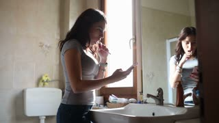Woman washing teeth while talking smart phone