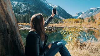 Woman Trying To Use Cell Phone In Nature