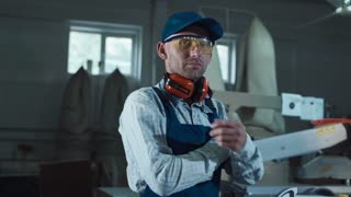 Worker man on protective headphones and eyeglasses standing with arms crossed in joinery shop