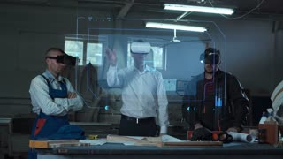 Workers and foreman using virtual reality headsets in carpentry workshop