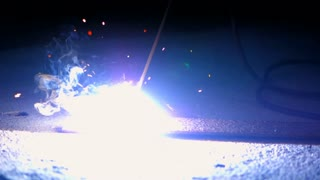 Workers grinding and welding in a factory. Welding on an industrial plant. Slow motion. Flashes and lot of sparks from welding work at construction site in dark
