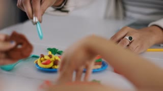 Young adult female plays with plasticine with a young child at a table
