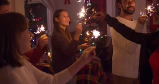 Young adult party-goers dance and play with sparklers at a holiday party - slow motion
