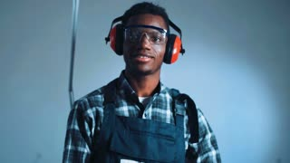 Young African-American man construction worker with angle grinder machine wearing safety ear muffs and checked shirt with overalls uniform, standing against white wall and smiling