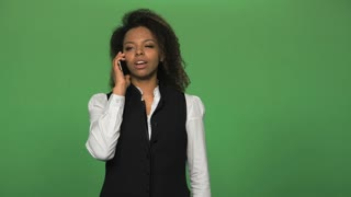 Young african business woman in formal suit answering and talking phone isolated on green background