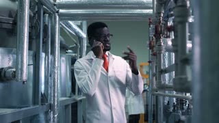 Young African man scientist talking phone walking in the factory. Horizontal indoors shot