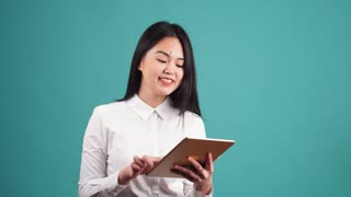 Young Asian Businesswoman Using Tablet Computer on Blue Background.